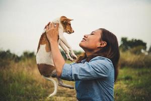 garota feliz alegre hipster brincando com seu cachorro no parque durante o pôr do sol foto