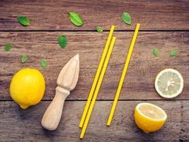 limão fresco, espremedor de sumos e canudos em um fundo de madeira foto