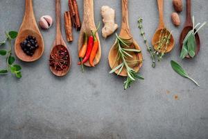 especiarias e ervas em colheres de madeira foto