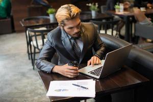jovem empresário segurando uma xícara de café enquanto trabalhava em um laptop em uma cafeteria foto