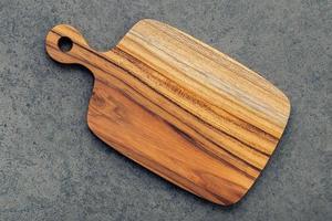 tábua de corte de madeira em fundo de pedra escura foto