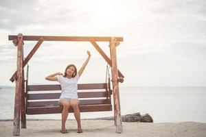 linda mulher se espreguiçando em um balanço na praia foto