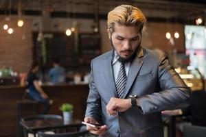 empresário falando no telefone olhando para o relógio foto