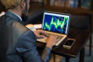 mãos de empresário digitando no teclado do laptop no local de trabalho foto