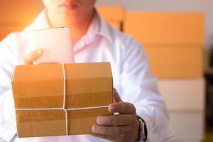 homem segurando um pacote e usa o telefone para fotografar foto
