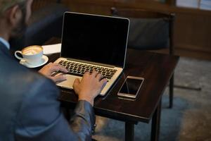 empresário digitando no teclado do laptop no local de trabalho foto