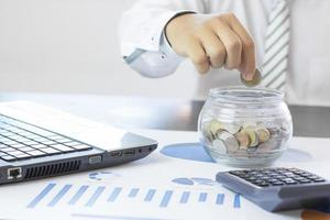 homem colocando moedas em uma jarra de vidro foto