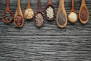 borda de grãos em colheres de madeira foto