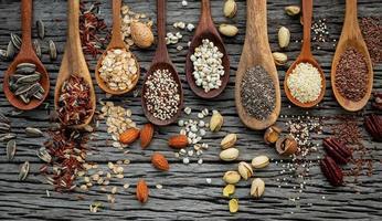 grãos e nozes em colheres em um fundo de madeira foto