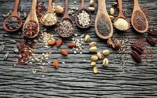grãos e nozes em colheres de madeira foto