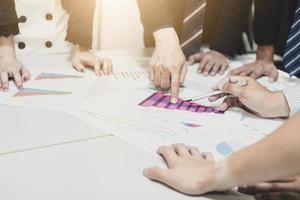 grupo de empresários planejando e analisando em uma mesa de reunião foto
