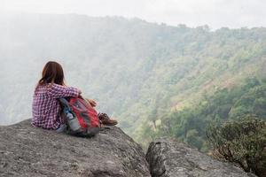 jovem alpinista com mochila sentado à beira de um penhasco foto