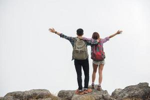 caminhantes com mochilas no topo de uma montanha apreciando a vista da natureza foto
