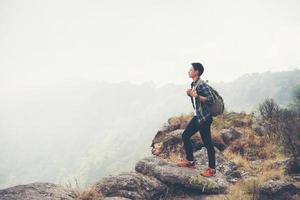 caminhante jovem hippie com mochila sentado no topo da montanha foto