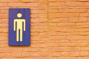 sinal de banheiro masculino na parede de tijolos foto