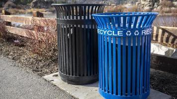 uma lixeira de metal preto e azul no parque