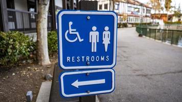 uma placa de banheiro de metal azul na rua