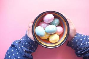 criança segurando uma tigela de ovos de páscoa em fundo rosa