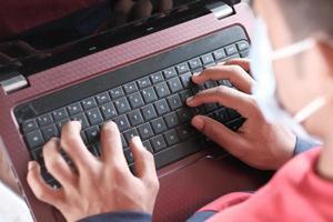 vista lateral de jovem com máscara cirúrgica usando laptop em casa foto