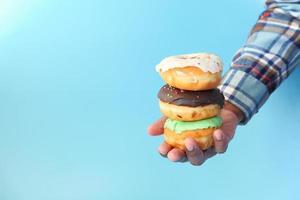 close-up de uma mão segurando donuts em fundo azul foto