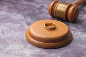 conceito de divórcio com martelo e anéis de casamento na mesa foto