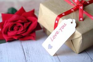 caixa de presente com etiqueta de amor e flor rosa em fundo branco foto