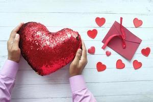 uma mão segurando um coração vermelho feito de lantejoulas na mesa, vista superior