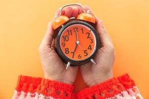 mão de uma mulher segurando um despertador em fundo laranja