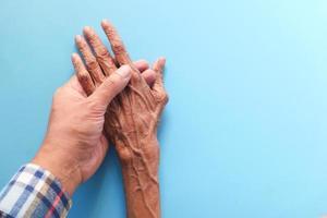 homem segurando a mão de uma mulher idosa em fundo azul foto