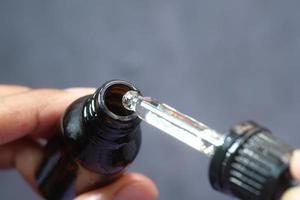 gota cai de uma pipeta em um frasco de cosmético foto