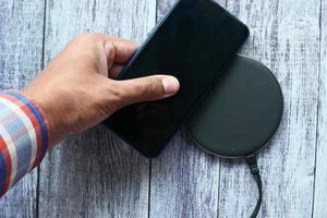 mão de homem carregando um smartphone com base de carregamento sem fio, vista superior foto