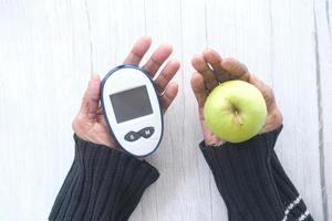 mulher sênior segurando ferramentas de medição para diabéticos e maçã na mesa de madeira