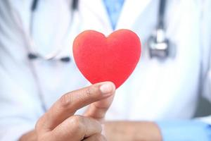 mão do médico segurando um coração vermelho, close-up foto