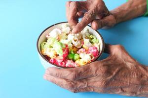 mãos de uma mulher idosa segurando uma tigela de pipoca colorida