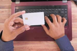 homem segurando um cartão de crédito e usando laptop para fazer compras online foto