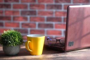 uma caneca de cor amarela, laptop e papel de carta em uma mesa ensolarada foto