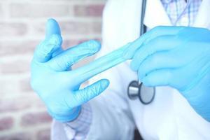 médico tirando luvas médicas, close-up foto