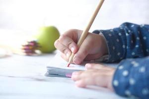 close-up da mão de uma criança desenhando com lápis colorido em uma página