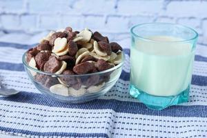 flocos de milho de chocolate em uma tigela e leite na mesa