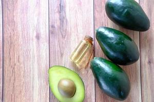 vista superior do óleo e uma fatia de abacate na mesa de madeira foto
