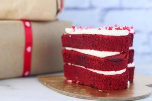 bolo em forma de coração, caixa de presente e flor rosa em fundo branco foto