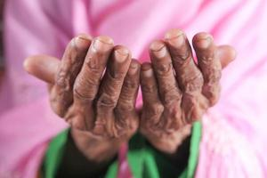 close-up das mãos de uma mulher idosa rezando no ramadã foto