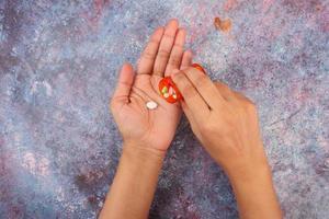 vista superior da mão de uma mulher tomando comprimidos na mesa