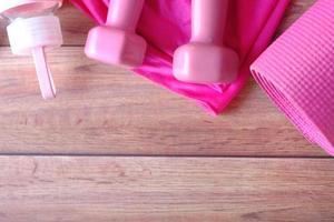 halteres de cor rosa, tapete para exercícios e garrafa de água no fundo de madeira foto
