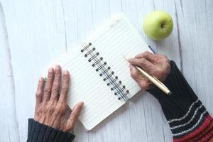 close-up da mão de uma mulher sênior escrevendo no bloco de notas