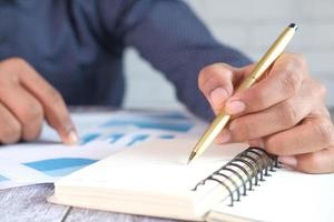 mão do homem com caneta, analisando dados financeiros e escrevendo no bloco de notas