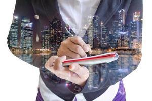 dupla exposição de empresária escrevendo em um bloco de notas com o horizonte da cidade à noite