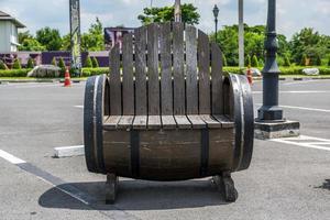 cadeira de madeira feita de um barril em um estacionamento foto
