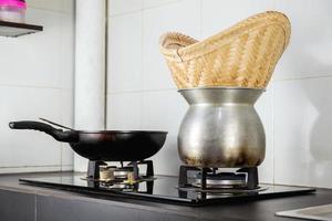 fogão a gás com panela e panela fumegante de arroz pegajoso e cesta