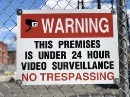 Proibida invasão e sinal de vigilância por vídeo do lado de fora em uma cerca de arame de metal